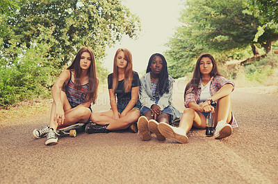 Buy stock photo Four young girls sitting in a road looking bored and displeased