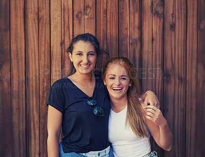 Buy stock photo Two teenage friends holding each other while standing outdoors on a warm Summer's day