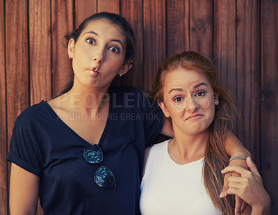 Buy stock photo Two young girls pulling funny faces outdoors
