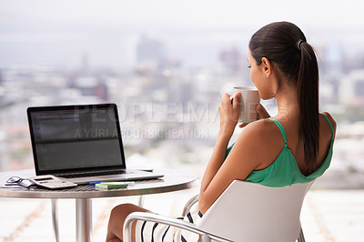 Buy stock photo A woman relaxing outdoors with her laptop and a cup of coffee