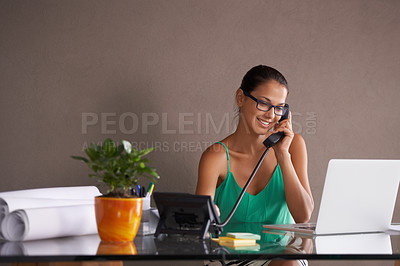 Buy stock photo A young woman taking a business call from her home office
