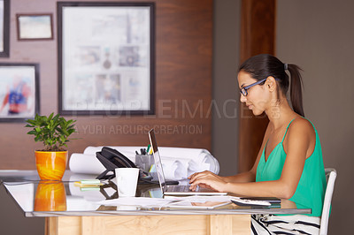 Buy stock photo A beautiful young woman typing on her laptop while sittting indoors