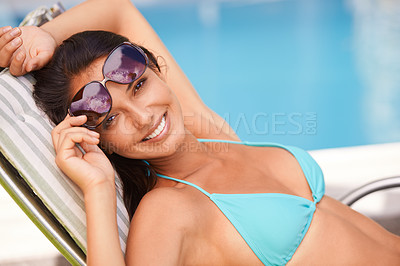 Buy stock photo Portrait of an attractive young woman relaxing beside a swimming pool