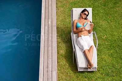 Buy stock photo A beautiful young woman reading a book while relaxing beside a swimming pool