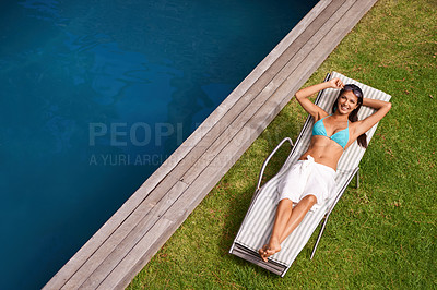 Buy stock photo Portrait of a beautiful young woman relaxing in a lounge chair by a swimming pool