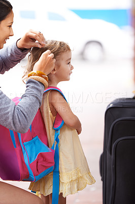 Buy stock photo A mother tying her daughter's hair while waiting for their transport to arrive