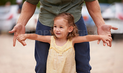 Buy stock photo A young girl holding on to her dad's fingers while they play outside