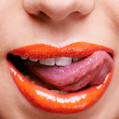 Buy stock photo Cropped shot of a woman licking her lips covered in shiny orange lipstick