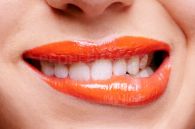 Buy stock photo Cropped shot of a woman biting her orange colored lips