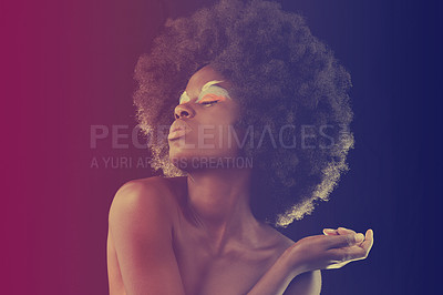 Buy stock photo A beautiful young model wearing colorful eye makeup posing in soft red light