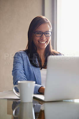 Buy stock photo Portrait of an attractive young businesswoman using a laptop at her office desk