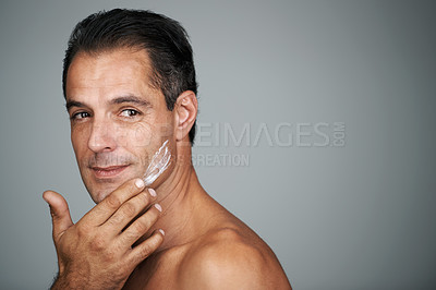 Buy stock photo Studio portrait of a handsome mature man applying moisturizer to his skin