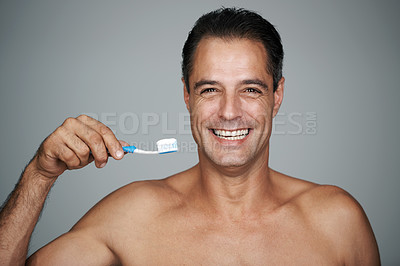 Buy stock photo Studio portrait of a handsome mature man holding up a toothbrush