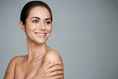 Buy stock photo Studio shot of a beautiful mature woman standing with her hand on her shoulder