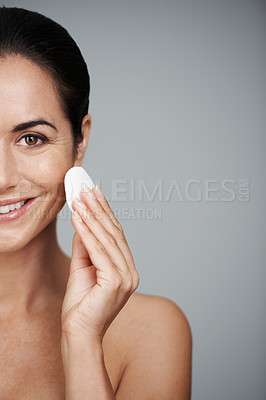 Buy stock photo Cropped shot of an attractive mid adult woman holding a cotton pad to her face