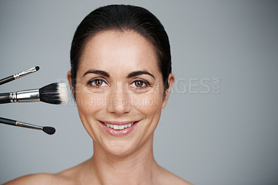 Buy stock photo Cropped studio portrait of a beautiful mid adult woman with make-up brushes next to her face