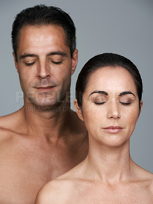 Buy stock photo Studio shot of a mature couple with their eyes shut standing together against a gray background
