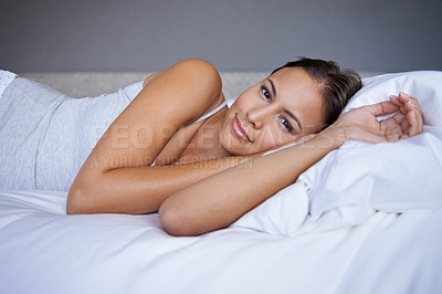 Buy stock photo Cropped shot of a young woman lying on a bed
