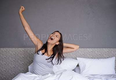 Buy stock photo Shot of a young woman yawning while stretching in bed
