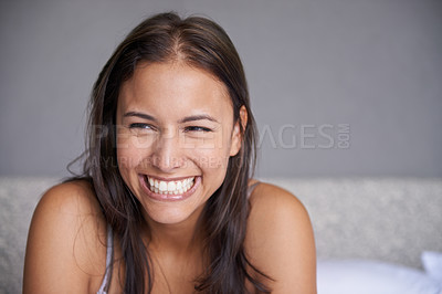 Buy stock photo Shot of a beautiful young woman with a big smile sitting on a bed
