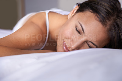 Buy stock photo Closeup shot of a young woman lying on a bed