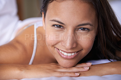 Buy stock photo Closeup portrait of a beautiful young woman lying on her bed