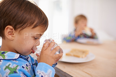Buy stock photo A cute little boy having a drink of water with breakfast