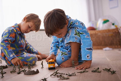 Buy stock photo Shot of two little boys playing with their toys on the floor