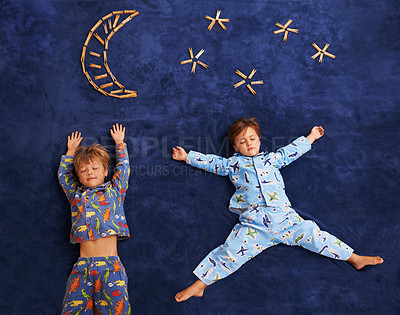 Buy stock photo Shot of two little boys lying on a carpet with their eyes shut