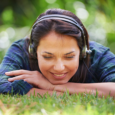 Buy stock photo Portrait of an attractive young woman lying on the grass and listening to music