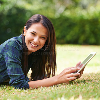 Buy stock photo Portrait of an attractive young woman lying on the grass using a digital tablet
