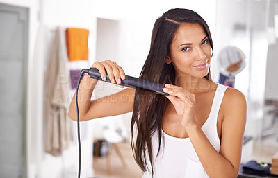 Buy stock photo Portrait of a beautiful young woman straightening her hair
