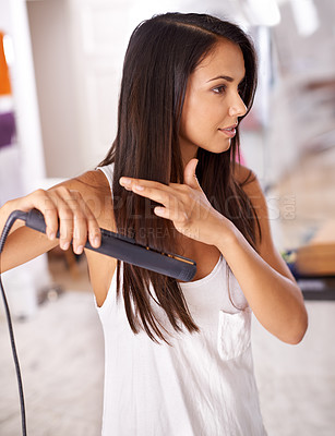 Buy stock photo Cropped shot of a beautiful young woman straightening her hair