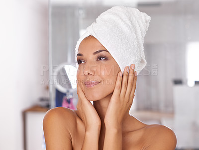 Buy stock photo Shot of a beautiful young woman standing in the bathroom with a towel wrapped around her head