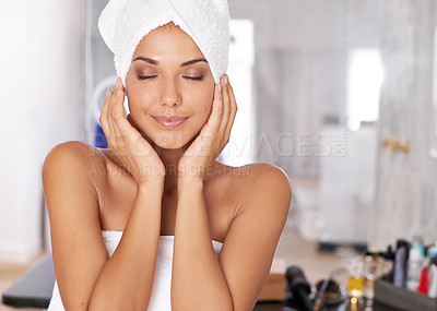 Buy stock photo Shot of a beautiful young woman standing in the bathroom in a towel