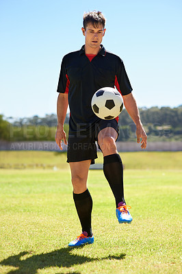 Buy stock photo Shot of a young footballer bouncing a ball on his knee