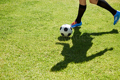 Buy stock photo Shot of a young footballer dribbling the ball on a field