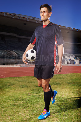 Buy stock photo Shot of a young footballer standing on a field holding a ball