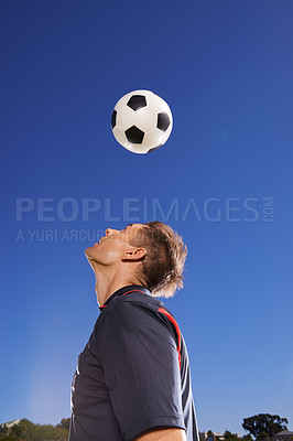 Buy stock photo Shot of a young footballer bouncing a ball on his head
