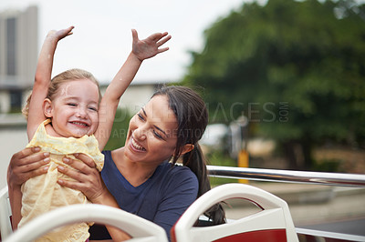Buy stock photo Shot of a mother holding on to her playful daughter while sitting on the bus