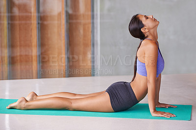 Buy stock photo A beautiful young woman doing yoga at home