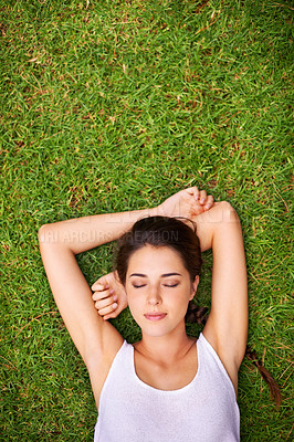 Buy stock photo Aerial shot of a young woman lying outside on the grass