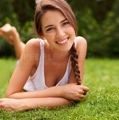 Buy stock photo Portrait of an attractive young woman lying on the grass