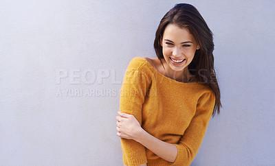 Buy stock photo Portrait of a beautiful young woman laughing while standing against a gray wall