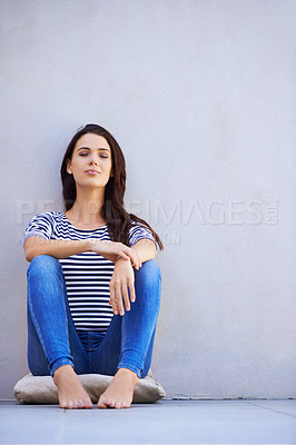 Buy stock photo Full-length shot of a beautiful young woman daydreaming while sitting on the floor
