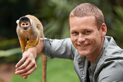 Buy stock photo Shot of a young man interacting with a little monkey at a wildlife park