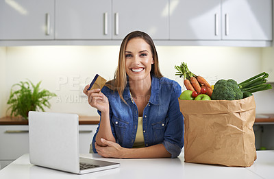 Buy stock photo Cropped shot of a young woman doing some online shopping with her groceries beside her