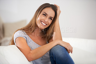 Buy stock photo Shot of a woman laughing on her sofa while looking away