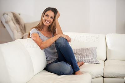 Buy stock photo Shot of a woman smiling at the camera while sitting on the sofa