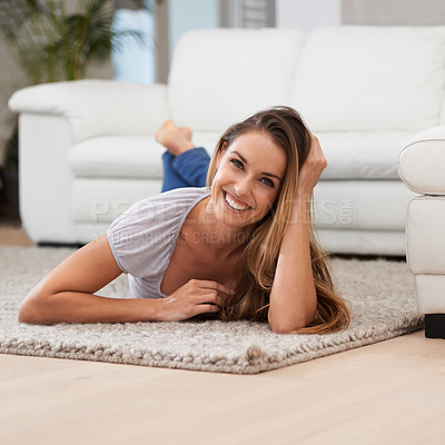 Buy stock photo A woman smiling at the camera while lying on her living room carpet